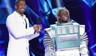 """This image released by Fox shows host Nick Cannon, left, with Lil Wayne in the third season premiere of """"The Masked Singer,"""" which aired on Sunday after the Super Bowl. The special edition of the show, with Lil' Wayne as the mystery guest, had its biggest audience ever Sunday when 23.7 million people watched it, the Nielsen company said. (Greg Gayne/FOX via AP)  **FILE**"""