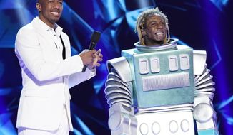 """This image released by Fox shows host Nick Cannon, left, with Lil Wayne in the third season premiere of """"The Masked Singer,"""" which aired on Sunday after the Super Bowl. The special edition of the show, with Lil' Wayne as the mystery guest, had its biggest audience ever Sunday when 23.7 million people watched it, the Nielsen company said. (Greg Gayne/FOX via AP)"""