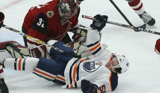 Edmonton Oilers right wing Kailer Yamamoto, right, is pulled down in front of Arizona Coyotes goaltender Antti Raanta (32) during the first period of an NHL hockey game Tuesday, Feb. 4, 2020, in Glendale, Ariz. (AP Photo/Ross D. Franklin)