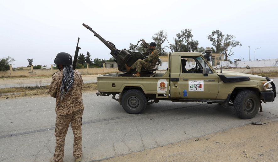 In this May 21, 2019 file photo, Tripoli government forces clash with forces led by Field Marshal Khalifa Hifter, south of the capital Tripoli, Libya. Two Libyan militia commanders and a Syrian war monitor group say Turkey is deploying Syrian extremists to fight in Libya's civil war. These extremists are affiliated with groups like al-Qaida and the Islamic State. They're fighting as mercenaries on behalf of the United Nations-supported government in Libya. The Libyan sources told The Associated Press that Turkey has airlifted more than 2,500 foreign fighters into Tripoli, and that dozens are extremist-affiliated. (AP Photo/Hazem Ahmed, File) **FILE**