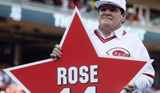 In this June 24, 2016, file photo, former Cincinnati Reds player Pete Rose (14) holds his place marker during a ceremony to honor the 1976 World Series champion team, before the Reds' baseball game against the San Diego Padres in Cincinnati.  (AP Photo/John Minchillo, File) **FILE**