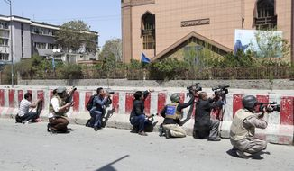 FILE- in this Saturday, April 20, 2019, photo, Afghan journalists work behind a barrier at the site of an attack on the Telecommunication Ministry in Kabul, Afghanistan. Limiting access to information by the Afghan government is not acceptable, said an official form an Afghan watchdog after around 30 media outlets protested severe limitation to information in Afghanistan. (AP Photo/Rahmat Gul, file)