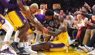 Los Angeles Lakers forward LeBron James I swarmed by teammates after making several 3-point shots in a row during the second half of the team's NBA basketball game against the San Antonio Spurs on Tuesday, Feb. 4, 2020, in Los Angeles. (AP Photo/Mark J. Terrill)  **FILE**