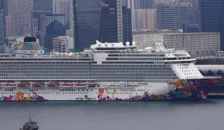 The World Dream cruise ship docked at Kai Tak cruise terminal in Hong Kong, Wednesday, Feb. 5, 2020. A Hong Kong official says more than 1,800 people on board the cruise ship that was turned away from a Taiwanese port will be quarantined until they are checked for a new virus. (AP Photo/Vincent Yu)