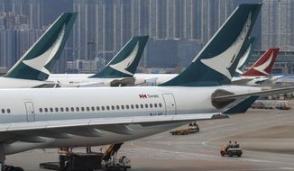 FILE - In this Aug. 12, 2019, file photo, ground crew drive past Cathay Pacific Airways planes park at the Hong Kong International Airport. Hong Kong airline Cathay Pacific Airways is asking its 27,000 employees to take three weeks of unpaid leave while the Hong Kong carrier struggles with plunging revenue due to China's virus outbreak. (AP Photo/Vincent Thian, File)