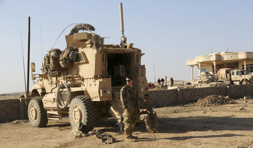 In this Feb. 23, 2017, photo, U.S. Army soldiers stand outside their armored vehicle on a joint base with the Iraqi army, south of Mosul, Iraq. (AP Photo/ Khalid Mohammed) **FILE**