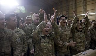 FILE - In this Dec. 26, 2018 file photo, members of the U.S. military cheer as President Donald Trump speaks at a hangar rally at Al Asad Air Base, Iraq The Iraqi government has told its military not to seek assistance from the U.S.-led coalition forces in operations against the Islamic State group, two senior Iraqi military officials said. The move comes amid a crisis of mistrust tainting U.S.-Iraq ties after an American airstrike ordered by President Donald Trump that killed Iranian Gen. Qassem Soleimani and senior Iraqi militia leader Abu Mahdi al-Muhandis. (AP Photo/Andrew Harnik, File)