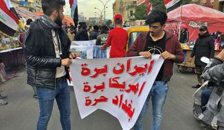 """In this Jan. 8, 2020 file photo, protesters hold a banner with Arabic that reads, """"Iran out, U.S. out, Baghdad is free"""" during a sit-in at Tahrir Square in Baghdad, Iraq. (AP Photo/Qassim Abdul-Zahra, File)"""
