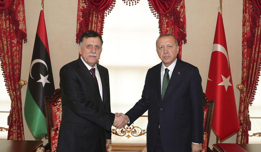 """FILE - In this Jan. 12, 2020 file photo, Turkey's President Recep Tayyip Erdogan, right, shakes hands with Fayez Sarraj, the head of Libya's internationally-recognized government, prior to their meeting in Istanbul. Two Libyan militia commanders and a Syrian war monitor group say Turkey is deploying Syrian extremists to fight in Libya's civil war. These extremists are affiliated with groups like al-Qaida and the Islamic State. They're fighting as mercenaries on behalf of the United Nations-supported government in Libya. The Libyan sources told The Associated Press that Turkey has airlifted more than 2,500 foreign fighters into Tripoli, and that """"dozens"""" are extremist-affiliated. (Turkish Presidency via AP, Pool, File)"""