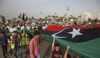 In this May 3, 2019, file photo, Libyans hold a demonstration against military operations by forces loyal to Field Marshal Khalifa Hifter, at Martyrs' Square in Tripoli, Libya. Two Libyan militia commanders and a Syrian war monitor group say Turkey is deploying Syrian extremists to fight in Libya's civil war. These extremists are affiliated with groups like al Qaeda and the Islamic State. They're fighting as mercenaries on behalf of the United Nations-supported government in Libya. (AP Photo/Hazem Ahmed, File)