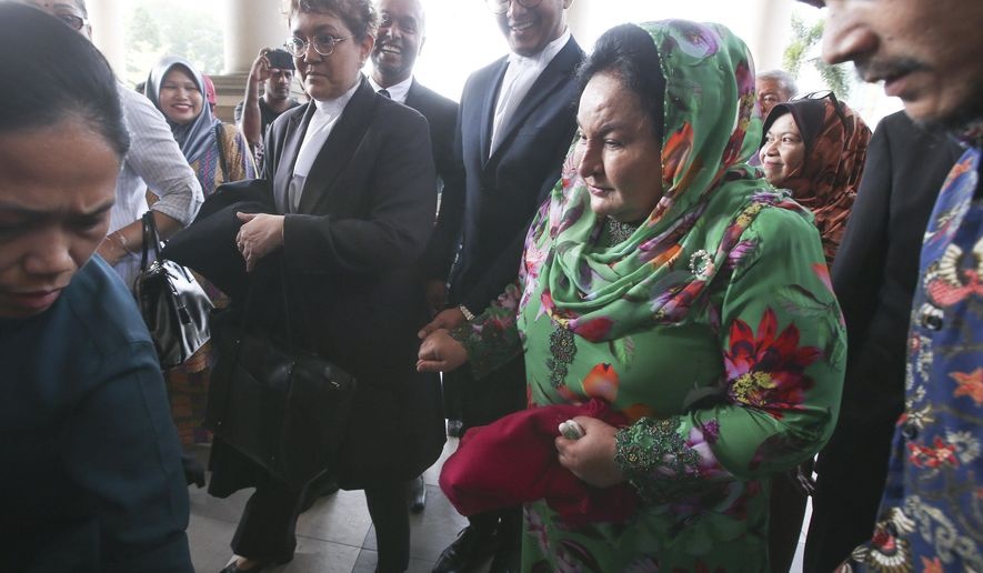 Rosmah Mansor, right, wife of former Malaysian Prime Minister Najib Razak, arrives at Kuala Lumpur High Court in Kuala Lumpur, Malaysia, Wednesday, Feb. 5, 2020. The graft trial of Rosmah has begun, with a top prosecutor saying she wielded considerable influence. (AP Photo)