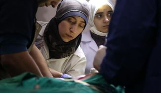 """This image released by National Geographic shows Dr. Amani, center, in the operating room in Syria in a scene from the Oscar nominated documentary """"The Cave."""" (National Geographic via AP)"""