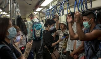 Commuters wear face masks to protect themselves from air pollution and the coronavirus on the BTS metro train in Bangkok, Thailand, Wednesday, Feb. 5, 2020. (AP Photo/Gemunu Amarasinghe)
