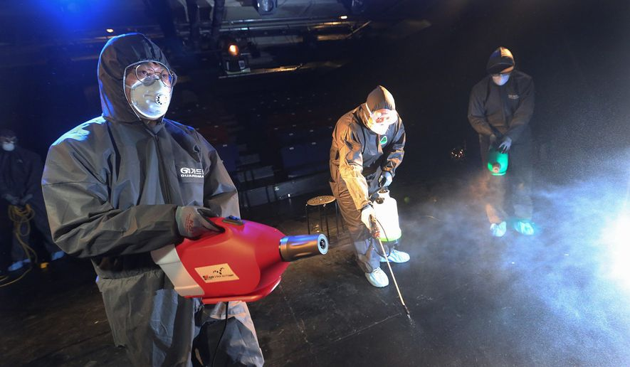 Workers wearing protective gear spray disinfectant as a precaution against a new coronavirus at a theater in Seoul, South Korea, on Thursday. More than two dozen U.S. forces and other deployed Americans are quarantined over virus exposure concerns. (ASSOCIATED PRESS)