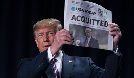 """President Donald Trump holds up a newspaper with the headline that reads """"ACQUITTED"""" at the 68th annual National Prayer Breakfast, at the Washington Hilton, Thursday, Feb. 6, 2020, in Washington. (AP Photo/ Evan Vucci)"""
