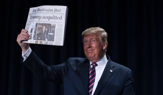 "President Donald Trump holds up a newspaper with the headline that reads ""Trump acquitted"" during the 68th annual National Prayer Breakfast, at the Washington Hilton, Thursday, Feb. 6, 2020, in Washington. (AP Photo/ Evan Vucci)"