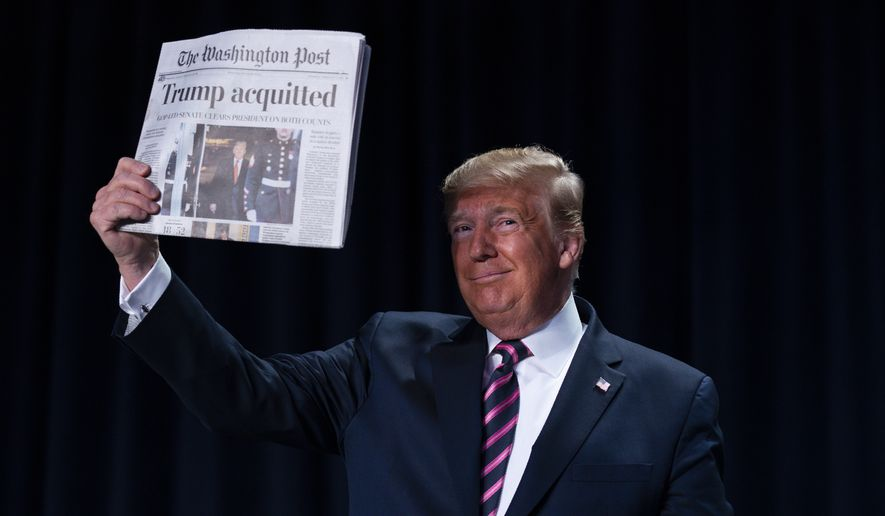 """President Donald Trump holds up a newspaper with the headline that reads """"Trump acquitted"""" during the 68th annual National Prayer Breakfast, at the Washington Hilton, Thursday, Feb. 6, 2020, in Washington. (AP Photo/ Evan Vucci)"""