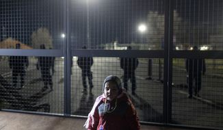 A child stands at the border line between Serbia and Hungary in Kelebija, Serbia, Thursday, Feb. 6, 2020. About two hundred migrants, including children, gathered Thursday at Serbia's border with Hungary to demand to be allowed entry into the European Union country. (AP Photo/Marko Drobnjakovic)