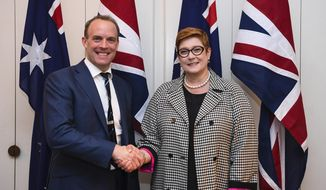 Britain's Foreign Secretary Dominic Raab, left, and Australian Foreign Minister Marise Payne pose for photographs ahead of a bilateral meeting at Parliament House in Canberra, Thursday, Feb. 6, 2020. (Lukas Coch/Pool Photo via AP)