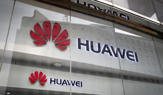 In this Jan. 29, 2019, file photo, the logos of Huawei are displayed at its retail shop window reflecting the Ministry of Foreign Affairs office in Beijing. (AP Photo/Andy Wong, File) **FILE**