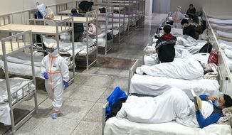 In this Wednesday, Feb. 5, 2020, photo, a medical worker in a protective suit walks by patients who diagnosed with the coronaviruses settle at a temporary hospital which transformed from an exhibition center in Wuhan in central China's Hubei province. (Chinatopix via AP)