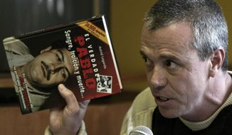 """FILE - In this June 27, 2006 file photo, Jhon Jairo Velasquez, a former hit man for Pablo Escobar, known by his nickname """"Popeye,"""" gives his testimony while holding a book titled """"The True Pablo, Blood, Treason, and Death,"""" during the trial against Alberto Santofimio Botero in Bogota, Colombia. According to authorities, Velasquez died of stomach cancer at a hospital in Bogota on Feb. 6, 2020. (AP Photo/William Fernando Martinez, File)"""