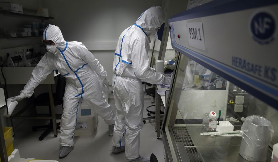 French lab scientists in hazmat gear inserting liquid in test tube manipulate potentially infected patient samples at Pasteur Institute in Paris, Thursday, Feb. 6, 2020. Scientists at the Pasteur Institute developed and shared a quick test for the new virus that is spreading worldwide, and are using genetic information about the coronavirus to develop a potential vaccine and treatments. (AP Photo/Francois Mori)