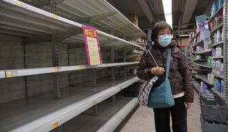 A woman wearing face mask walks past empty shelf of tissue papers at supermarket in Hong Kong, Thursday, Feb. 6, 2020. Ten more people were sickened with a new virus aboard one of two quarantined cruise ships with some 5,400 passengers and crew aboard, health officials in Japan said Thursday, as China reported 73 more deaths and announced that the first group of patients were expected to start taking a new antiviral drug. (AP Photo/Vincent Yu)