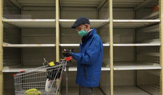 A man wearing face mask stands near an empty shelf of rice at a supermarket in Hong Kong, Thursday, Feb. 6, 2020. Ten more people were sickened with a new virus aboard one of two quarantined cruise ships with some 5,400 passengers and crew aboard, health officials in Japan said Thursday, as China reported 73 more deaths and announced that the first group of patients were expected to start taking a new antiviral drug. (AP Photo/Vincent Yu)