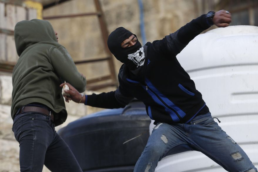 Palestinian protesters hurl stones towards Israeli soldiers during clashes in the West Bank city of Hebron, Thursday, Feb. 6, 2020. Israeli forces have killed two Palestinians in clashes in the occupied West Bank and a third in Jerusalem after he opened fire at a police officer. The killings came hours after a car-ramming attack elsewhere in the city Thursday wounded 12 Israeli soldiers. Tensions have soared following last week's release of President Donald Trump's Mideast initiative, which greatly favors Israel and was rejected by the Palestinians. (AP Photo/Majdi Mohammed)
