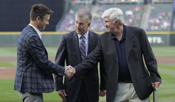 In this Aug. 3, 2018 file photo, Seattle Mariners general manager Jerry Dipoto, left, President Kevin Mather, center, and owner John Stanton, right, take part in a ceremony before a baseball game against the Toronto Blue Jays in Seattle. Spring training for the Mariners ahead of the 2020 season will feature young players and prospects that could be at the heart of whether the Mariners' rebuild plans ultimately work. (AP Photo/Ted S. Warren, File)  **FILE**