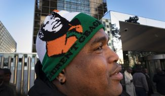 A supporter of former Ivory Coast president Laurent Gbagbo shows his headwear outside the International Criminal Court in The Hague, Netherlands, Thursday, Feb. 6, 2020. The ICC hears an appeal by Gbagbo against conditions imposed on him and a former government minister during their release from custody pending prosecutors' appeal against their acquittals on crimes against humanity charges. (AP Photo/Peter Dejong)