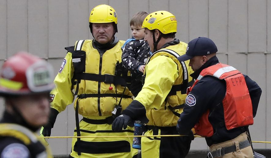 A firefighter carries Harlyn Alves, 2 years old, along a rope line and to high ground as his four-member family was evacuated from their apartment building Thursday, Feb. 6, 2020, in Issaquah, Wash. Heavy rain sent the creek over a major roadway, under an apartment building east of Seattle and up to the foundations of homes as heavy rains pounded the region. A flood watch was in effect through Friday afternoon across most of western Washington. Numerous roads were closed because of water over the roadway. Officials also warned of landslide risks. (AP Photo/Elaine Thompson)