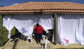 In this Tuesday, Feb. 4 photo, Martin G. Brumbaugh School kindergarten teacher Nydsy Santiago walks past curtains set up to provide shade for her students under a gazebo at a municipal athletic park in Santa Isabel, Puerto Rico. Some children in Puerto Rico have been left out of school nearly a month after a 6.4-magnitude earthquake hit the island and forced officials to permanently close dozens of public schools, prompting more homeschooling and some teachers to voluntarily find an appropriate outdoor location and resume classes with permission from parents. (AP Photo/Carlos Giusti)