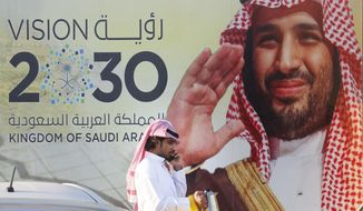"In this Wednesday, Feb. 5, 2020, photo, a Saudi man carries his coffee pot as he walks past a banner showing Saudi Crown Prince Mohammed bin Salman, outside a mall in Jiddah, Saudi Arabia. Human rights organization Amnesty International says Saudi Arabia has used a special anti-terrorism court as ""a weapon of repression"" to imprison peaceful critics, dissidents, activists, journalists, clerics and members of the kingdom's minority Muslim Shiites, including some who were sentenced to death and executed. (AP Photo/Amr Nabil)"