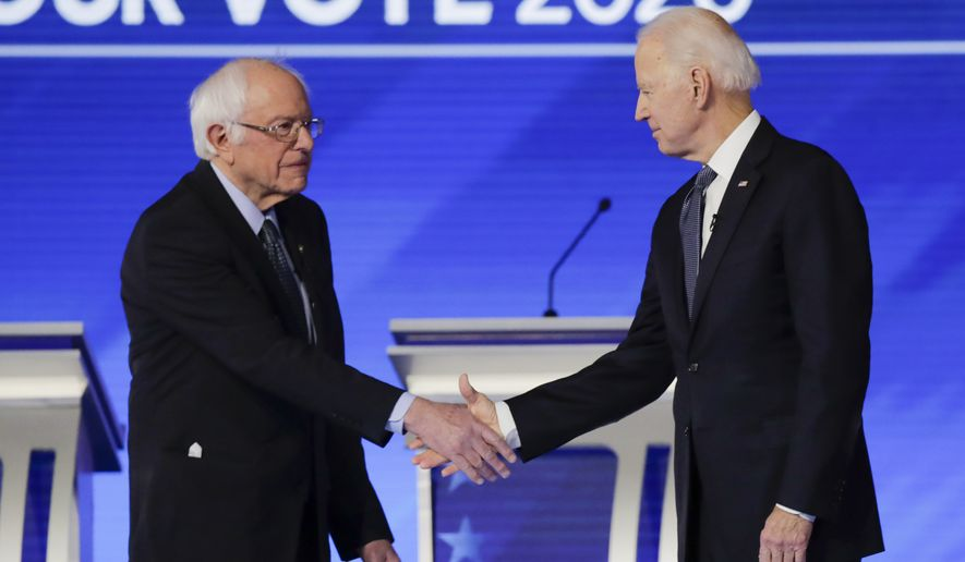 Democratic presidential candidates Sen. Bernie Sanders, I-Vt., left, and former Vice President Joe Biden, shake hands on stage Friday, Feb. 7, 2020, before the start of a Democratic presidential primary debate hosted by ABC News, Apple News, and WMUR-TV at Saint Anselm College in Manchester, N.H. (AP Photo/Charles Krupa) ** FILE **