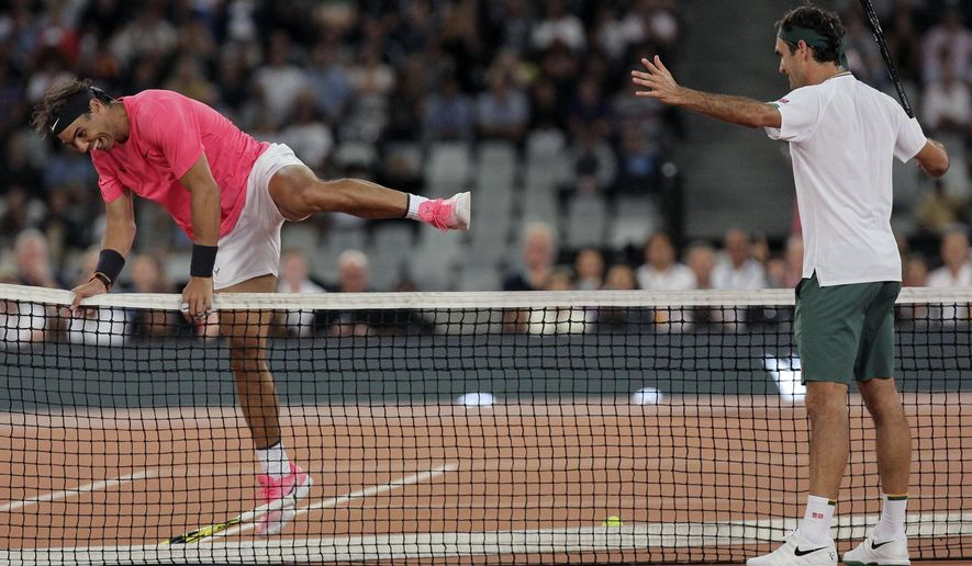 Rafael Nadal, left, jumps the net while Roger Federer watches on during their exhibition tennis match held at the Cape Town Stadium in Cape Town, South Africa, Friday Feb. 7, 2020. (AP Photo/Halden Krog)