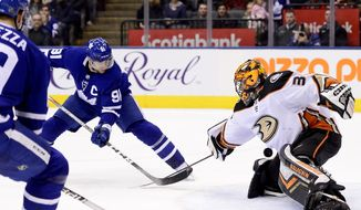 Toronto Maple Leafs center John Tavares (91) knocks the puck past Anaheim Ducks goaltender John Gibson (36) to score in overtime during an NHL hockey game Friday, Feb. 7, 2020, in Toronto. (Frank Gunn/The Canadian Press via AP)