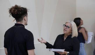 FILE - In this Oct. 1, 2019, file photo, Gory Rodriguez, of Starbucks, right, interviews a job applicant during a job fair at Dolphin Mall in Miami. The January U.S. jobs report on Friday, Feb. 7, 2020, may provide timely evidence of the U.S. economy's enduring health. (AP Photo/Lynne Sladky, File)