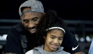 In this July 26, 2018, file photo former Los Angeles Laker Kobe Bryant and his daughter Gianna watch during the U.S. national championships swimming meet in Irvine, Calif. Federal investigators say wreckage from the helicopter that crashed last month and killed Bryant, his daughter and seven others did not show any outward evidence of engine failure, the National Transportation Safety Board said Friday, Feb. 7, 2020. (AP Photo/Chris Carlson,File)
