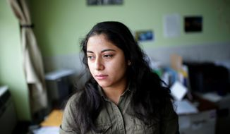 This photo taken Dec. 21, 2019, shows  Maudy Constanza, 24, whose had her family divided as they tried to come to the United States to seek asylum. She and her two young daughters are in Ashland, Mass, while her husband and son were sent to Nuevo Laredo, a Mexican border town, under the Trump administration's Remain in Mexico policy. The ACLU is bringing a lawsuit on Costanza's behalf against the program. (Jonathan Wiggs/The Boston Globe via AP)