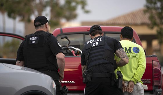 In this July 8, 2019, photo, a U.S. Immigration and Customs Enforcement (ICE) officers detain a man during an operation in Escondido, Calif. A federal judge has prohibited U.S. immigration authorities from relying on databases deemed faulty to ask law enforcement agencies to hold people in custody, a setback for the Trump administration that threatens to hamper how it carries out arrests. (AP Photo/Gregory Bull)