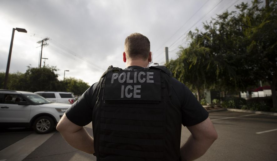 FILE - In this July 8, 2019, file photo, a U.S. Immigration and Customs Enforcement (ICE) officer looks on during an operation in Escondido, Calif. A federal judge has prohibited U.S. immigration authorities from relying on databases deemed faulty to ask law enforcement agencies to hold people in custody, a setback for the Trump administration that threatens to hamper how it carries out arrests (AP Photo/Gregory Bull, File)