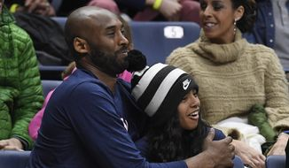 In this March 2, 2019, file photo Kobe Bryant and his daughter Gianna watch the first half of an NCAA college basketball game between Connecticut and Houston in Storrs, Conn. A public memorial service for Bryant, Gianna and seven others killed in a helicopter crash is planned for Monday, Feb. 24, 2020, at Staples Center in Los Angeles, a person with knowledge of the details told The Associated Press on Thursday, Feb. 6, 2020. (AP Photo/Jessica Hill, File)  **FILE**