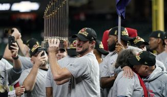 In this Oct. 30, 2019, file photo, Washington Nationals starting pitcher Max Scherzer celebrates with the trophy after Game 7 of the baseball World Series against the Houston Astros in Houston. The Nationals head to spring training with mostly the same squad that won the World Series. They are counting again on being led by a star-studded rotation featuring Scherzer and Stephen Strasburg, along with slugger Juan Soto. (AP Photo/David J. Phillip, File)  **FILE**