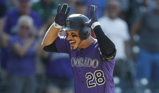 FILE In this Aug. 14, 2019, file photo, Colorado Rockies' Nolan Arenado celebrates as he circles the bases after hitting a walkoff, two-run home run off Arizona Diamondbacks relief pitcher Archie Bradley in the ninth inning of a baseball game in Denver. Arenado is at odds with the team's front office as the Rockies head to spring training for the season ahead. (AP Photo/David Zalubowski, File)