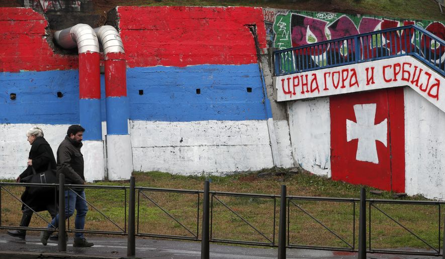 """People walk by graffiti showing a Serbian flag, left, and text reading """"Montenegro and Serbia'' in Belgrade, Serbia, Monday, Jan. 27, 2020. (AP Photo/Darko Vojinovic)"""