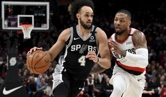 San Antonio Spurs guard Derrick White, left, drives to the basket against Portland Trail Blazers guard Damian Lillard, right, during the first half of an NBA basketball game in Portland, Ore., Thursday, Feb. 6, 2020. (AP Photo/Steve Dykes)
