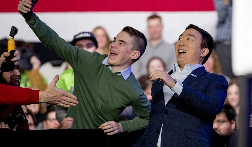 "Democratic presidential candidate Andrew Yang takes a photograph with a member of the audience as he arrives at ""Our Rights, Our Courts"" forum New Hampshire Technical Institute's Concord Community College, Saturday, Feb. 8, 2020, in Concord, N.H. (AP Photo/Andrew Harnik)"
