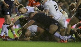 England's Ellis Genge, bottom left, scores a try in Storm Ciara during the Six Nations rugby union international match between Scotland and England at Murrayfield Stadium, in Edinburgh, Scotland, Saturday, Feb. 8, 2020. (AP Photo/Scott Heppell)